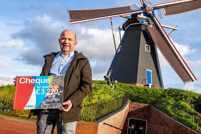 Jan van der Lee van de stichting met de cheque voor de herbouwde molen.