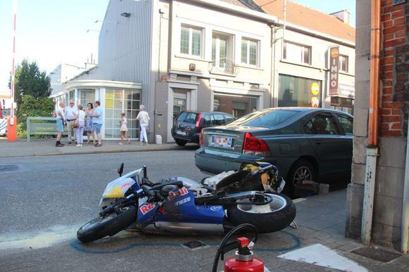 De motard schoof met zijn moto onder de koffer van een geparkeerde wagen.
