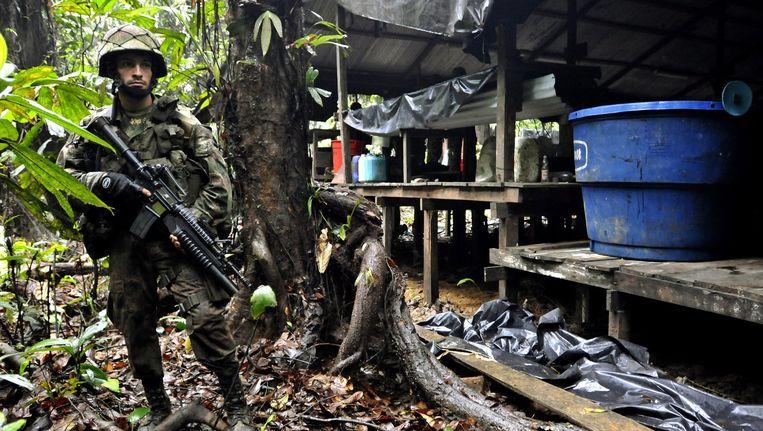 Een Colombiaanse soldaat bewaakt een cocaïnelaboratorium van Farc. Beeld epa
