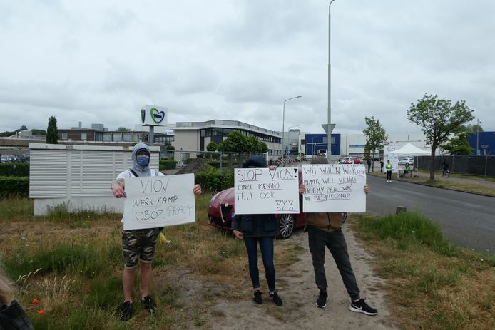 Drie van de vier jonge Poolse demonstranten bij de poort van slachterij Vion in Boxtel. Ze vragen aandacht voor veilige werkomstandigheden in verband met corona.