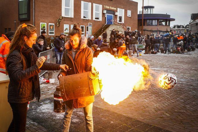 Op oudejaarsdag werd er volop geschoten met melkbussen en carbid op het Havenplein in Genemuiden. Op de achtergrond 't Olde Staduus en het met linten afgezette bordes.