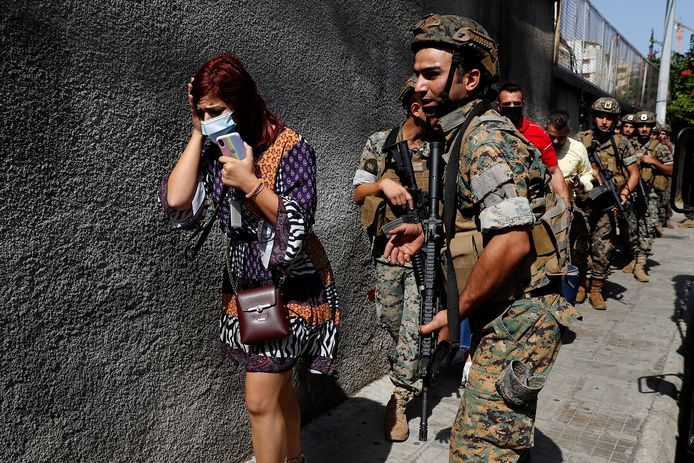 Des soldats des forces spéciales de l'armée libanaise protègent des enseignants qui fuient leur école après les affrontements meurtriers qui ont éclaté sur une ancienne ligne de front de la guerre civile de 1975-90 entre les zones musulmanes chiites et chrétiennes, dans le quartier d'Ain el-Remaneh, à Beyrouth, au Liban, ce jeudi 14 octobre 2021.