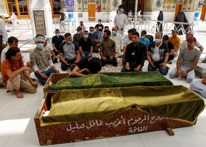 Families rouwen bij de kisten met lichamen van slachtoffers.