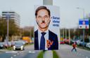 Een bekladde VVD-verkiezingsposter met het gezicht van Mark Rutte hangt aan de Statenweg in Rotterdam.