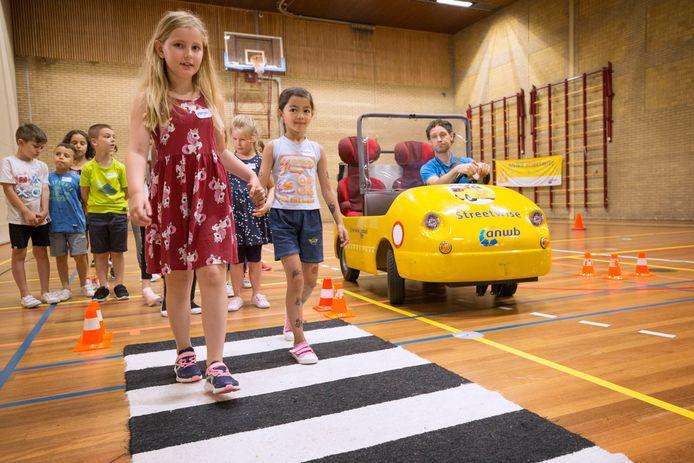 Kinderen krijgen verkeersveiligheidsles van de ANWB. Hier leren ze waar ze op moeten letten voor het oversteken. Foto: Pix4Profs/Joyce van Belkom