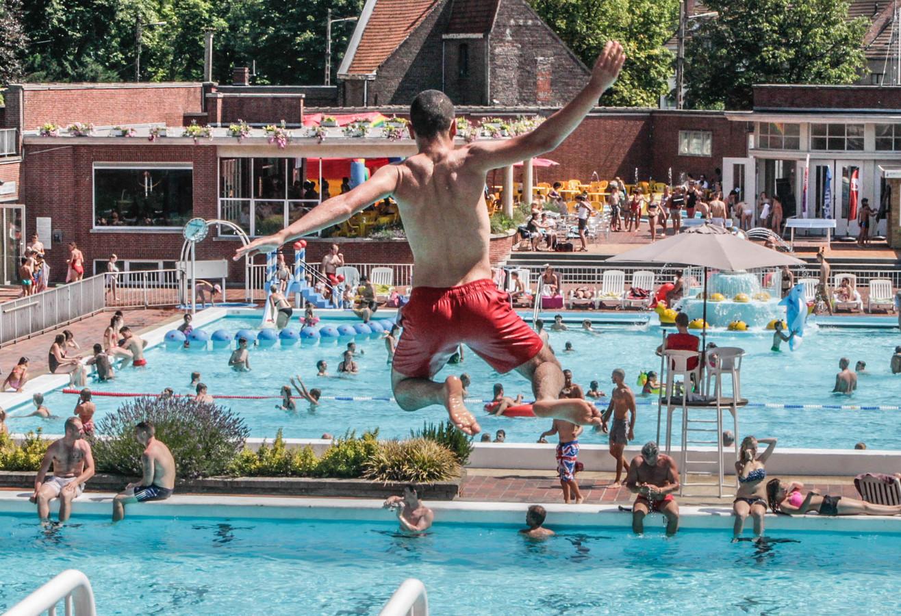Een jongen springt van de drie meter hoge duikplank in het openluchtbad in de Abdijkaai. Dit is een archiefbeeld uit 2017.