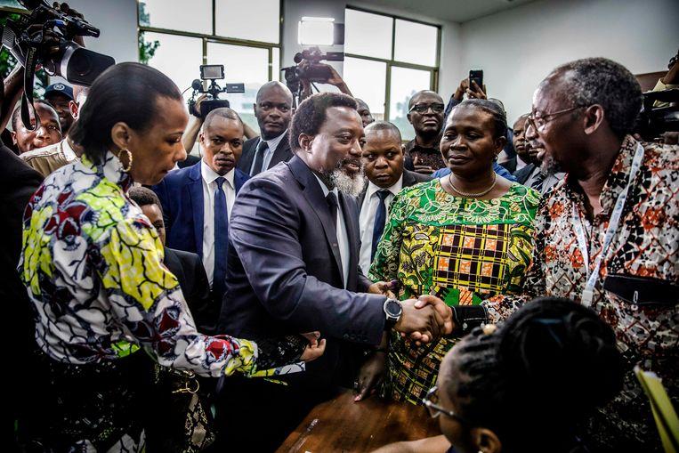 Afscheidnemend president Joseph Kabila begroet enkele kiezers nadat hij zijn stem uitgebracht heeft in Kinshasa. Beeld AFP