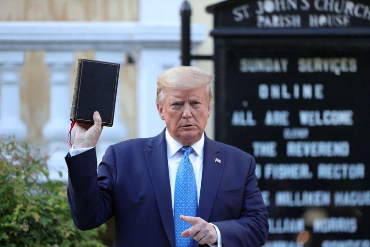 Oud-president Donald Trump met een bijbel voor de Episcopaalse kerk nabij het Witte Huis. Om de foto te kunnen laten maken gebruikte de federale politie onder meer traangas om demonstranten uiteen te drijven.  Beeld REUTERS