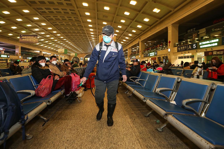 Een personeelslid ontsmet de wachtzaal in het treinstation van Wuhan, enkele dagen geleden.