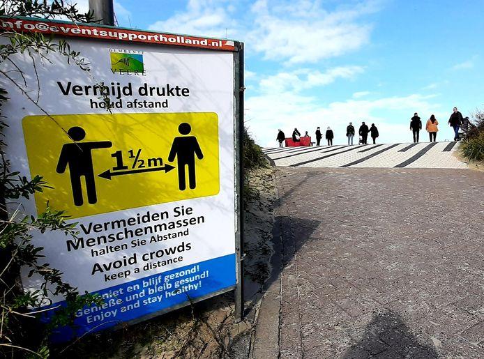Bord 'Vermijd drukte' bij strandovergang Domburg.