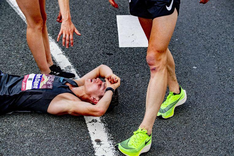 Een renner ligt uitgeteld op de grond na de finish van de race. Beeld ANP
