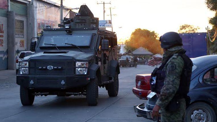 Mexicaanse soldaten bewaken het lijkenhuis in Apatzingan waar Enrique 'Kike' Plancarte ligt opgebaard. Beeld afp