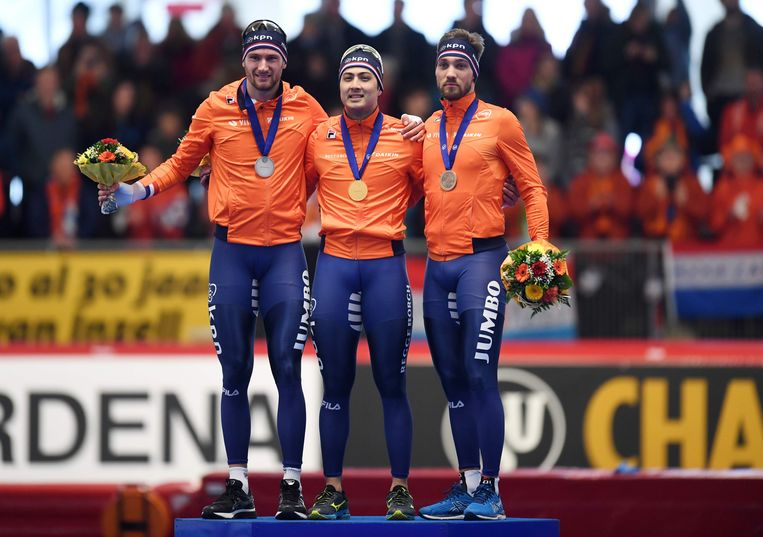 Thomas Krol (links), Kai Verbij (midden) en Kjeld Nuis worden gehuldigd voor hun prestaties op de 1000 meter in Inzell.  Beeld AFP