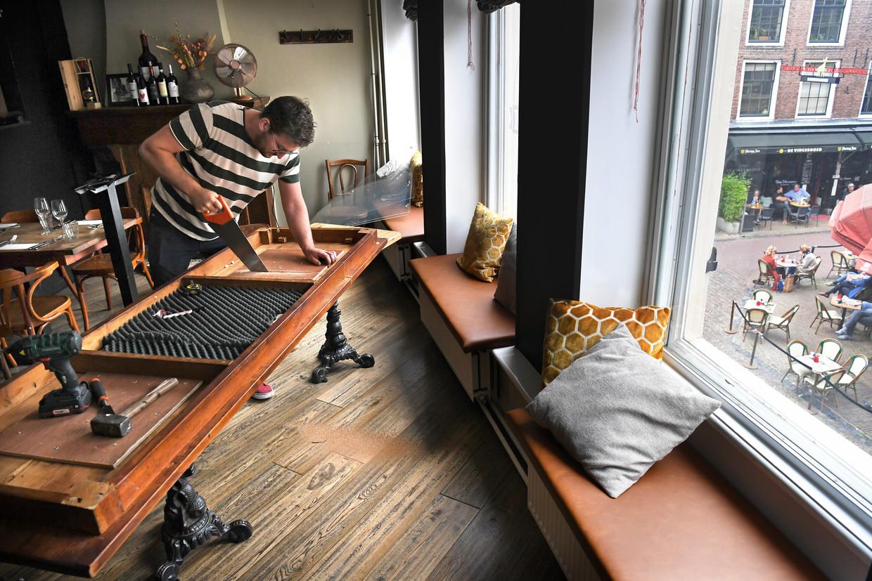 Rutger van Bijlevelt (28) zaagt een tafelblad doormidden zodat hij er twee nieuwe tafels van kan maken. Beeld Marcel van den Bergh / de Volkskrant