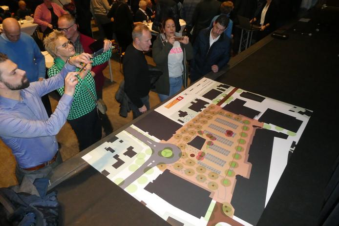 Bezoekers aan de informatie-avond in D'n Durpsherd maken met hun mobieltjes foto's van het nieuwe ontwerp van het Mercuriusplein.