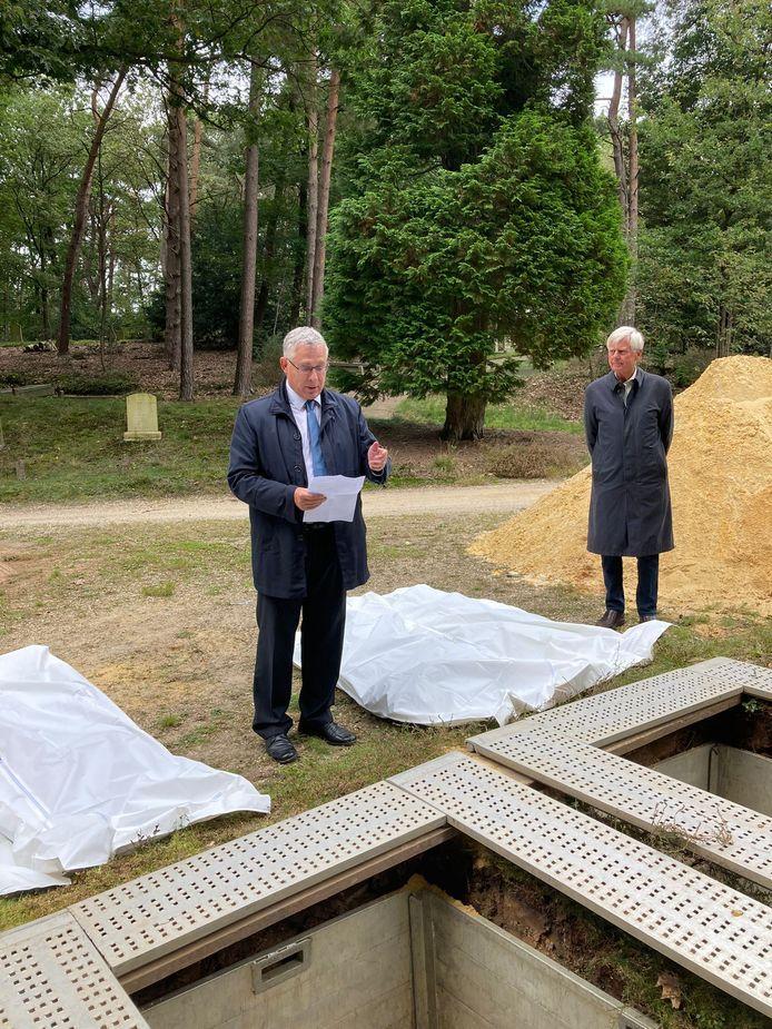 Wethouder Marc Budel (links) bij de herbegeraving van botresten van mensen uit de middeleeuwen.