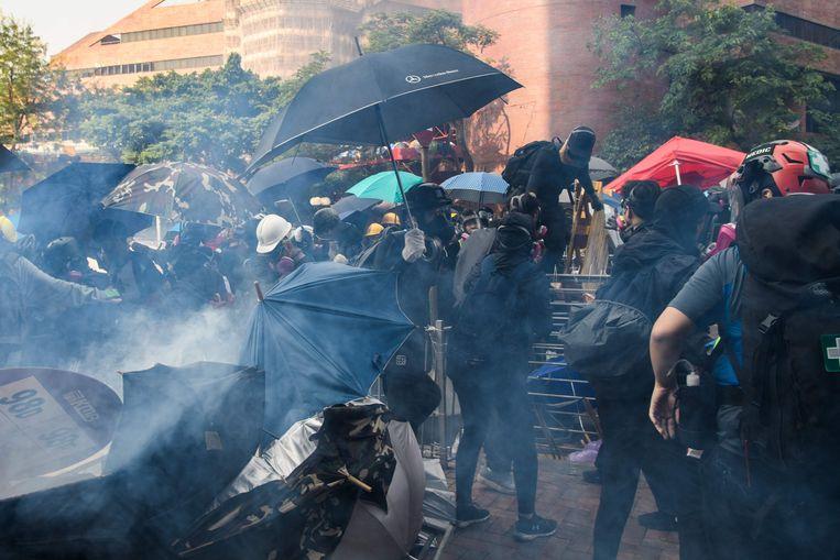 Demonstranten rennen weg van het traangas dat de politie afvuurt aan de universiteitscampus. Beeld AFP