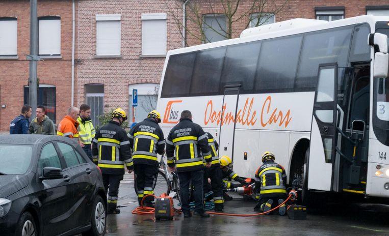 De brandweer bij de bus, die omhoog getild werd om de fiets - en even daarvoor ook het meisje zelf - er vanonder te halen.