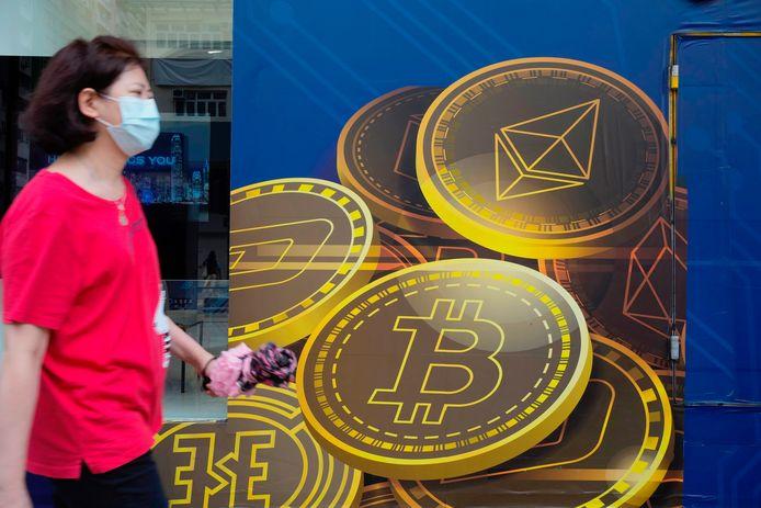 Een vrouw wandelt voorbij een advertentie voor cryptomunten in Hong Kong.