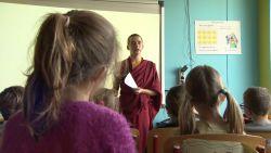 Monnik Giel geeft kinderen les over boeddhisme