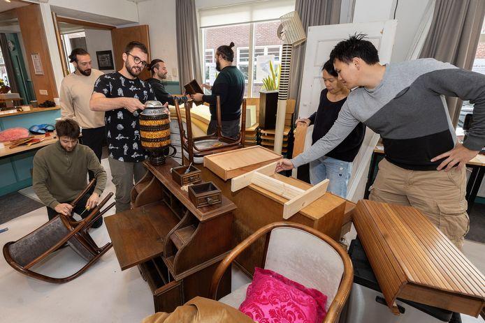 Italiaanse designers en enkele buurtbewoners ontfermen zich over ingeleverde meubelstukken in buurthuis De Buut in de Rochusbuurt in Eindhoven. Uiterst links zit Giorgio Gasco. Daarnaast Marco Cagnoni en Gianmaria Della Ratta.