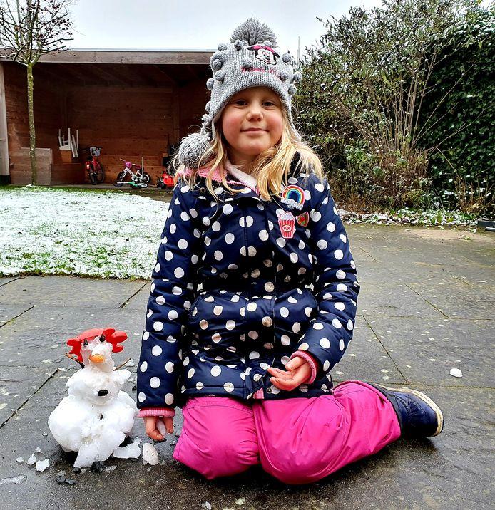 Ook met weinig sneeuw weet Evelien (6) uit Schalkhaar een sneeuwpop(je) te maken.