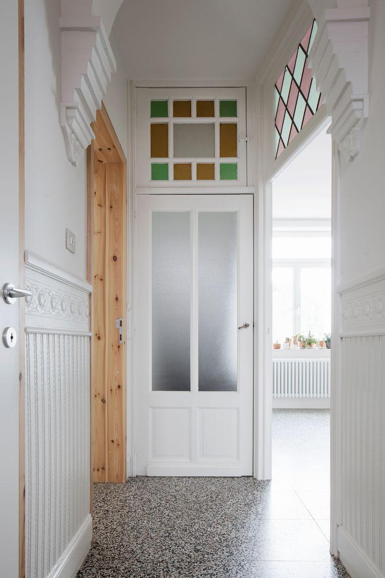 Authentieke elementen zoals de binnendeuren met glas in lood, de moulures in de gang en de verborgen glaspartij aan de trap werden in hun oorspronkelijke staat hersteld. Beeld Johnny Umans