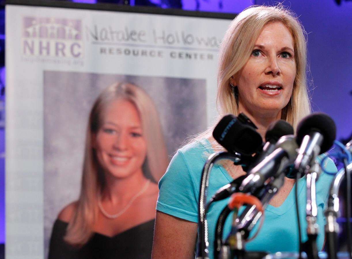 Foto uit 2010 van Beth Holloway met op de achtergrond een afbeelding van haar dochter Natalee.