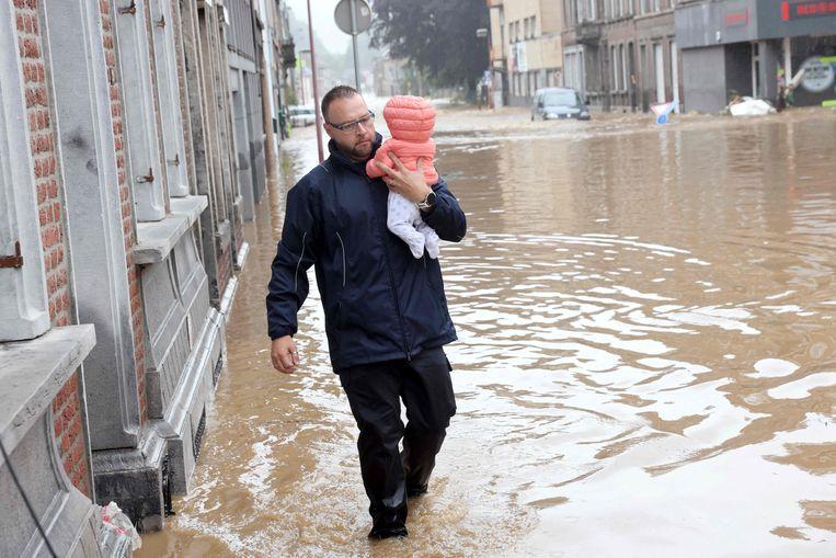 Een vader brengt zijn baby in veiligheid in het ondergelopen Hognoul (Awans, provincie Luik).  Beeld AFP