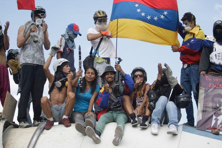 Wuilly Arteaga steekt zijn viool omhoog tijdens een protestmars in Caracas, Venezuela. De beroemde violist was ooit lid van El Sistema. Beeld AP