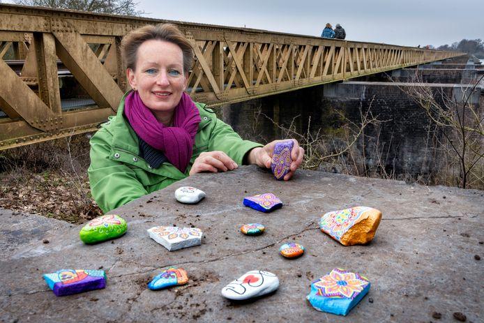 Lisette van Maasakker met haar happy stones. Ze verstopt ze onder meer bij de Moerputtenbrug bij Den Bosch.