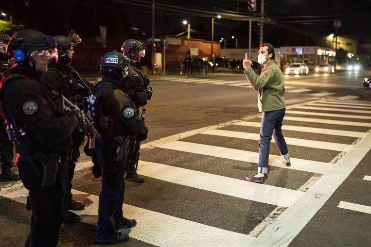 Een demonstrant reageert zijn woede af op de politie in Portland. Beeld AFP