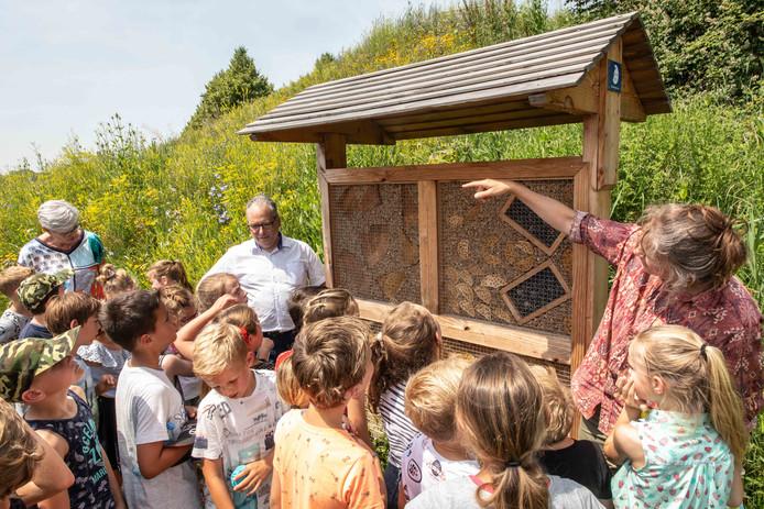 Sylvia Tuinder geeft de kinderen uitleg over het bijenhotel aan de rand van woonwijk Mannee.