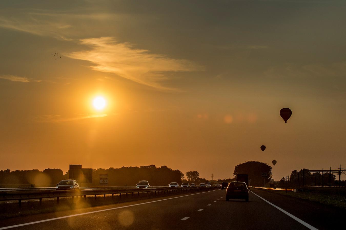 Luchtballonnen bij een ondergaande zon, gezien vanaf de snelweg A15.