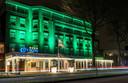 Het City Hotel in Oss, badend in het licht. Er worden straks honderd arbeidsmigranten gehuisvest.