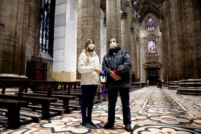 Toeristen met mondkapjes in de Duomo Kathedraal in Milaan, op 2 maart 2020.  Beeld EPA