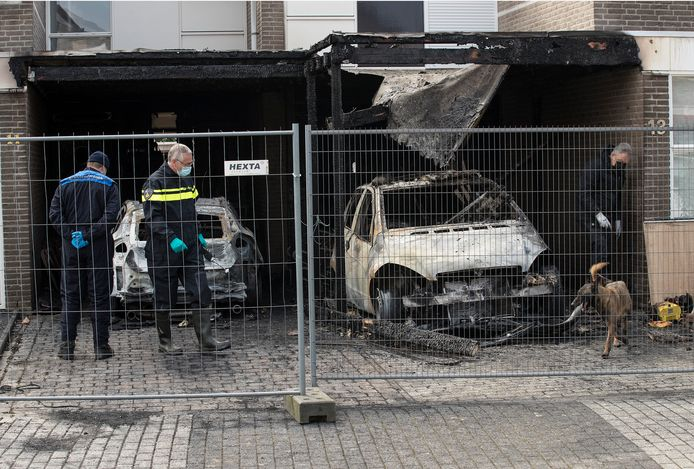 Een politiehond wordt ingezet bij het onderzoek naar de oorzaak van de brand in 's-Heerenberg.
