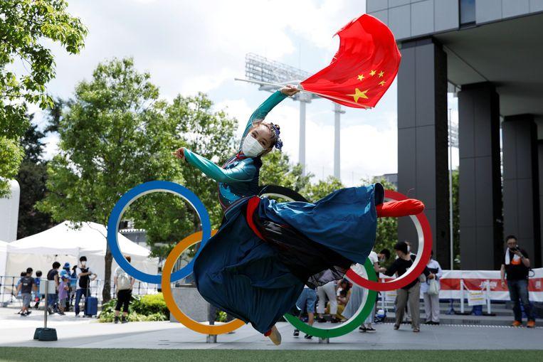 Een traditionele Chinese dans bij de olympische ringen bij het Olympisch Stadion in Tokio. China ging aan het eind van de donderdag aan kop in het medailleklassement. Beeld REUTERS