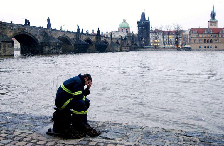 Een brandweerman rust uit aan de kant van de overstroomde rivier Vltava in Praag. Beeld afp