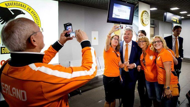 Guus Hiddink poseert donderdag na aankomst op de luchthaven van Riga voor de foto met Oranjefans. Beeld anp