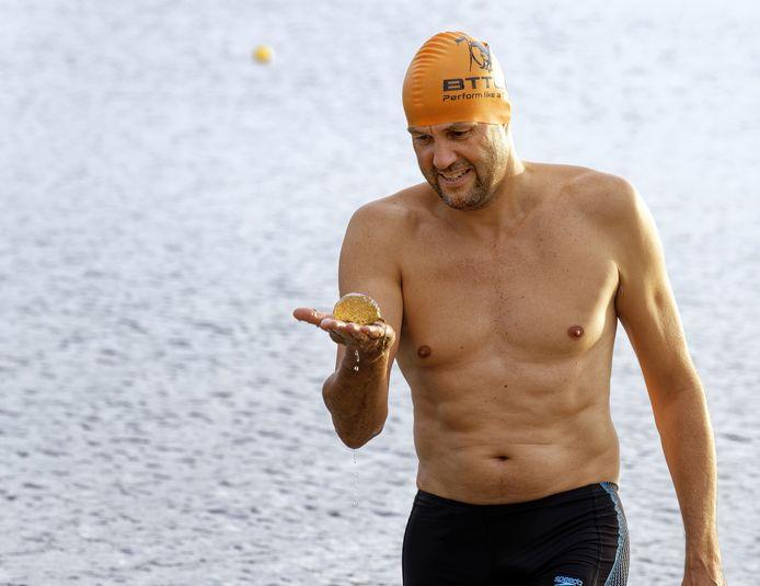 Een zwemmer in de IJzeren Man van Dommelbaarzen duikt een bal watermosdiertjes op.
