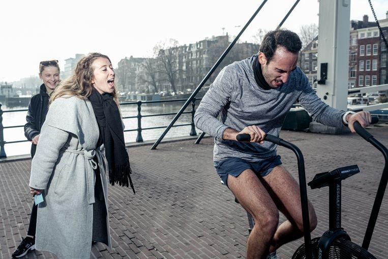 Een deelnemer van het hardloopevent wordt aangemoedigd, terwijl hij zich  op de Airbike in het zweet werkt.  Beeld Jakob van Vliet