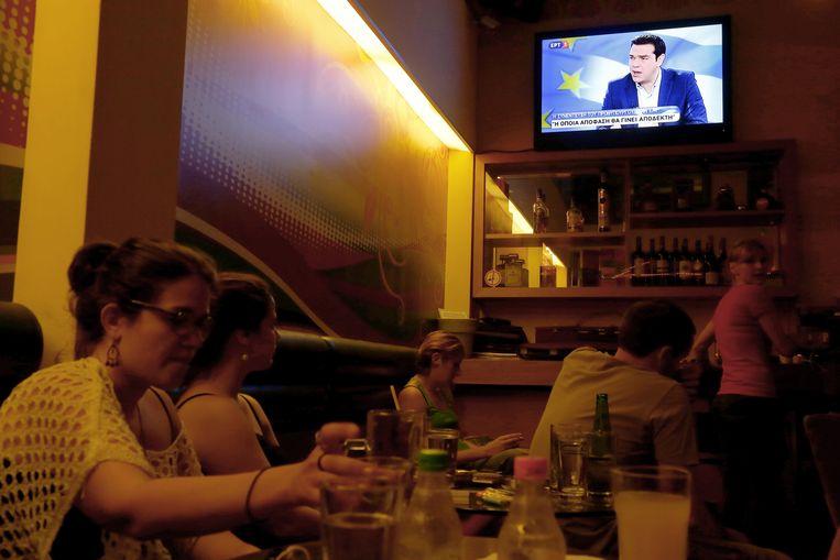 Grieken kijken op restaurant naar het interview met premier Tsipras. Beeld AP