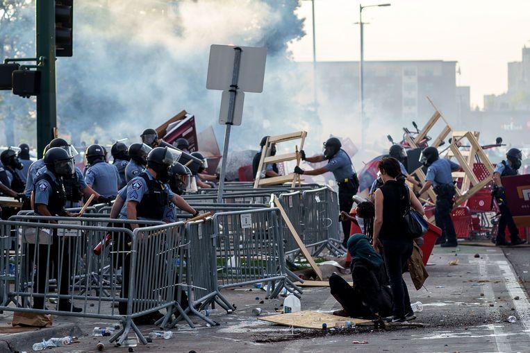 Agenten halen een barricade weg bij het politiebureau dat later in brand zou worden gestoken. Beeld Kerem Yucel / AFP