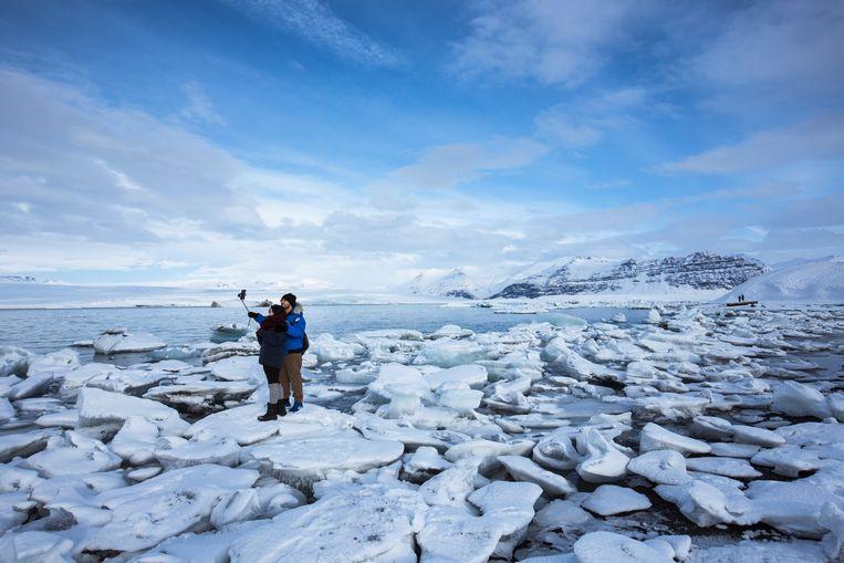 Toeristen nemen een selfie op Jökulsárlón, het grootste gletsjermeer in IJsland.  Beeld Tim Graham / Getty