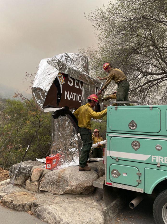 Brandweerlieden wikkelen welkomstborden van het park in folie, ter bescherming tegen de bosbranden.