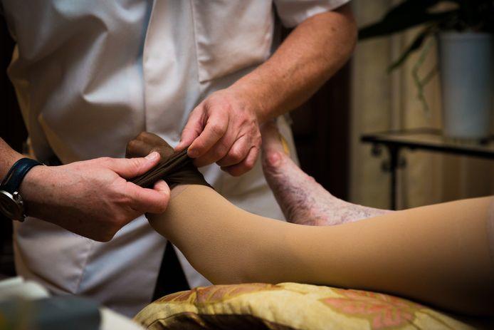 Een zorgmedewerker helpt met steunkousen.