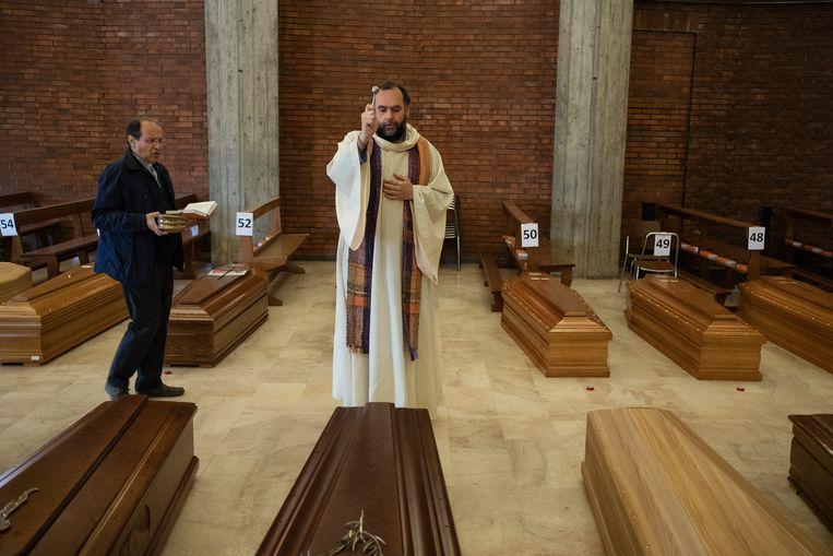 Don Mario Carminati (rechts), pastoor in Bergamo, en zijn collega Don Marcello zegenen de kisten van de slachtoffers. De begrafenisondernemer komt de twee ingepakte kisten zo halen. Beeld Giulio Piscitelli