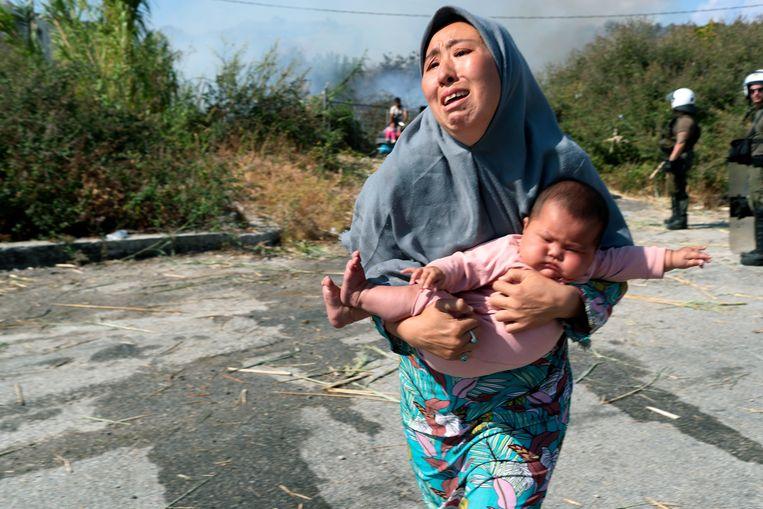 Een vrouw brengt haar baby in veiligheid. Duizenden asielzoekers op Lesbos werden dakloos nadat branden het vluchtelingenkamp Moria in de as legden.  Beeld AP