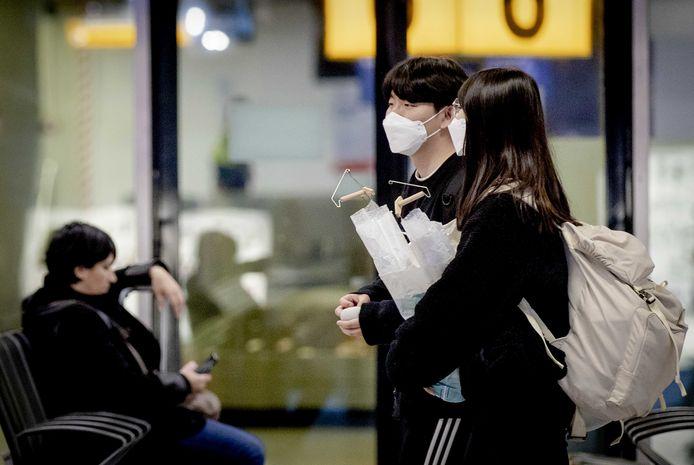 Reizigers op Schiphol met een mondkapje.